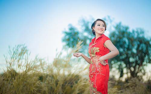 A Chinese woman from Shenzhen China in a traditional Chinese dress posing for a photo.