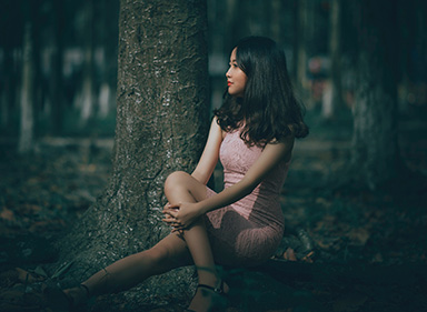 A young Chinese girl sitting under the tree.